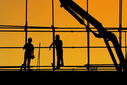 silhouette of two men building a house